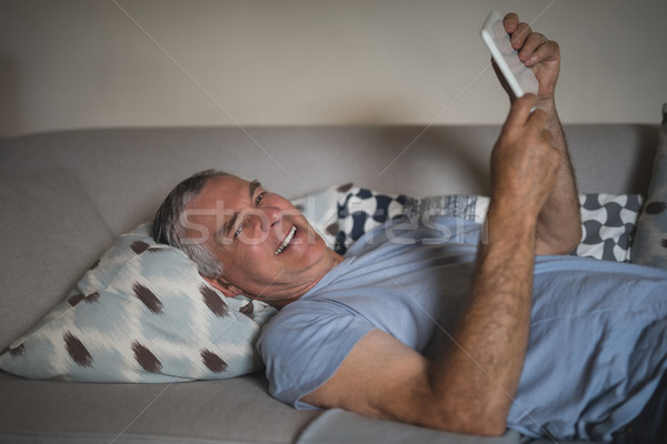 Smiling senior man holding digital tablet while lying on sofa at home Stock photo © wavebreak_media
