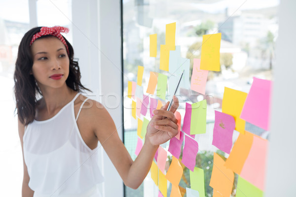 Female executive pointing at sticky note in office Stock photo © wavebreak_media