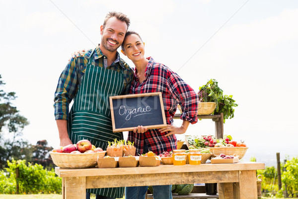Portrait of couple with blackboard selling organic vegetables Stock photo © wavebreak_media