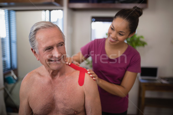 Vrouwelijke arts elastisch tape schouder Stockfoto © wavebreak_media
