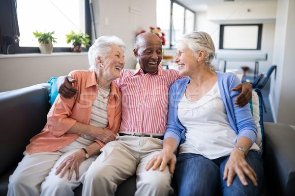 Smiling senior man sitting with arm around over females Stock photo © wavebreak_media