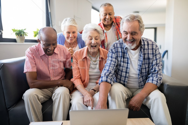 Cheerful senior friends looking at laptop on table Stock photo © wavebreak_media