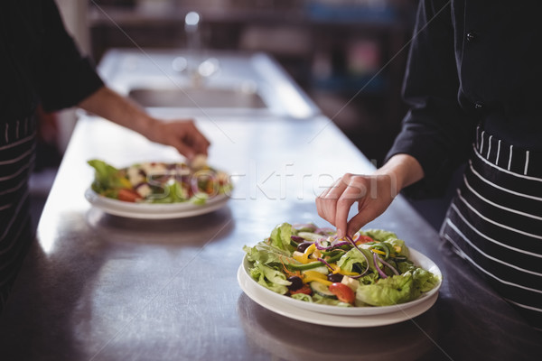 Midsection of waiter and waitress preparing fresh salad in commercial kitchen Stock photo © wavebreak_media