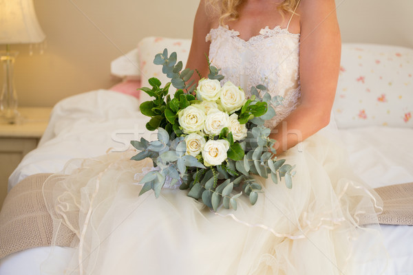 Midsection of bride in wedding dress holding bouquet while sitting on bed Stock photo © wavebreak_media