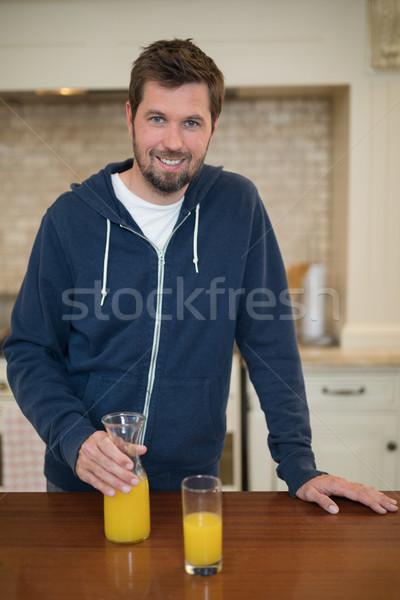 Man holding glass of juice in the kitchen Stock photo © wavebreak_media
