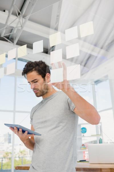 Człowiek patrząc cyfrowe tabletka karteczki biuro Zdjęcia stock © wavebreak_media