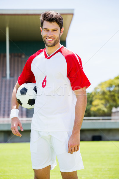 Happy football player standing with a ball Stock photo © wavebreak_media