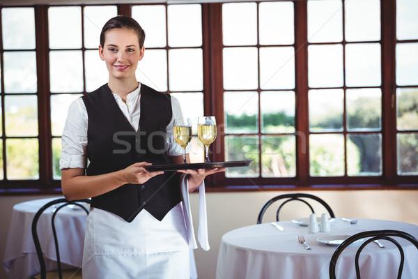 Smiling waitress holding a tray with glasses of wine Stock photo © wavebreak_media