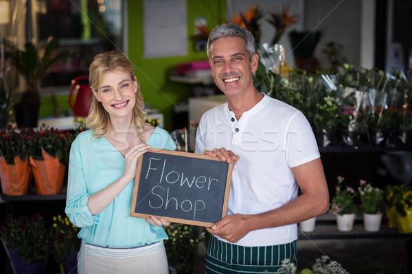 Smiling florists holding flower shop sign on slate in flower sho Stock photo © wavebreak_media
