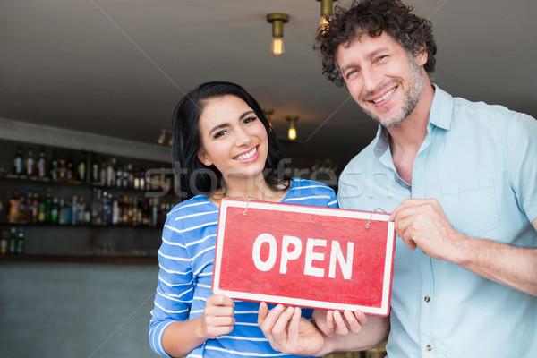 Couple holding open signboard Stock photo © wavebreak_media