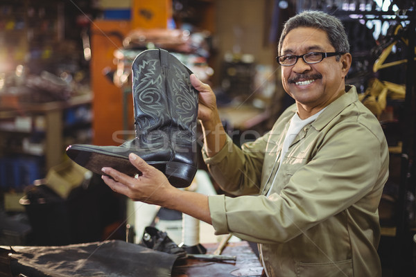 Portrait of smiling shoemaker holding a leather boot Stock photo © wavebreak_media