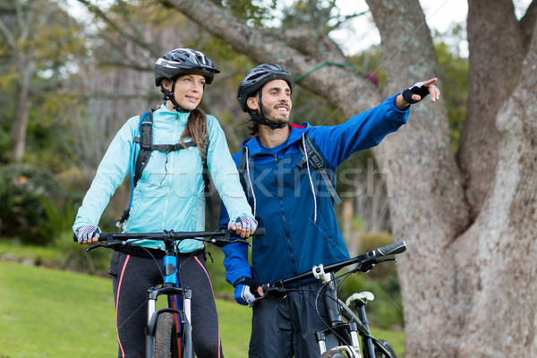 Biker couple with mountain bike pointing in distance Stock photo © wavebreak_media