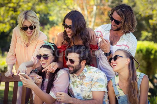 друзей глядя мобильного телефона улыбаясь парка Сток-фото © wavebreak_media