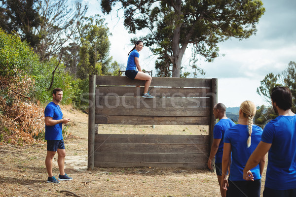 Fit woman sitting over wooden wall during obstacle course Stock photo © wavebreak_media