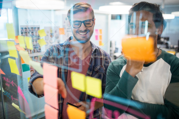 Stock photo: Smiling creative business team reading sticky notes