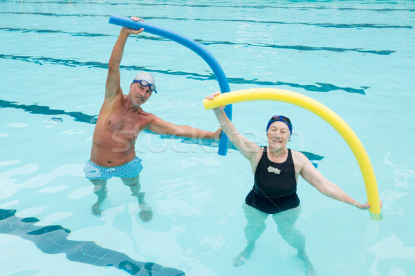 Senior couple exercising with pool noodle in swimming pool Stock photo © wavebreak_media