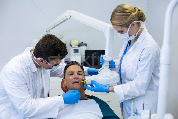 Dentists examining a male patient with tools Stock photo © wavebreak_media
