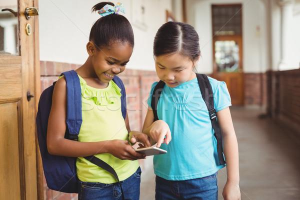 Cute uczniowie patrząc smartphone korytarz dziewczyna Zdjęcia stock © wavebreak_media