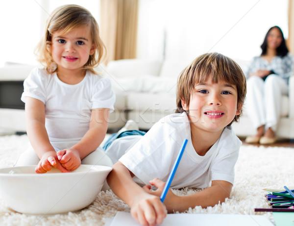 Cheerful siblings eating chips and drawing  Stock photo © wavebreak_media