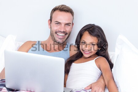 Radiant couple using a laptop on a bed Stock photo © wavebreak_media