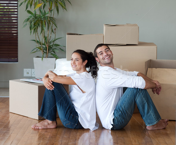Bright couple with unpacking boxes moving to a new house Stock photo © wavebreak_media