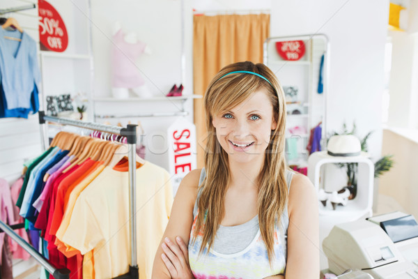 Stock photo: Attractive young woman smiling at the camera standing in a clothes store