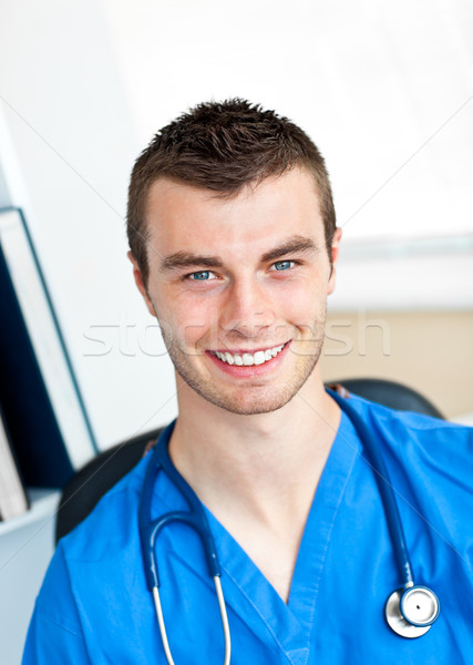 Smiling surgeon looking at the camera wearing scrubs sitting in a office Stock photo © wavebreak_media