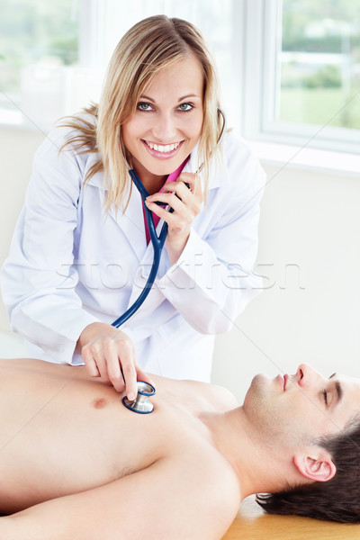 beautiful female doctor using stethoscope on a patient lying in her office Stock photo © wavebreak_media