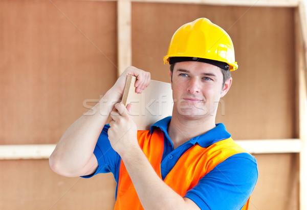 Tolakodó fiatal férfi munkás citromsárga sisak Stock fotó © wavebreak_media