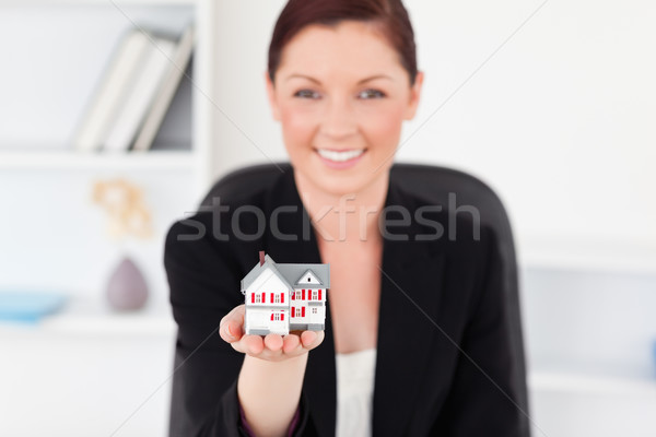 Pretty red-haired woman in suit holding a miniature house while sitting in an office Stock photo © wavebreak_media