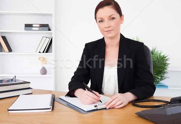 Attractive red-haired female in suit writing on a notepad and posing while sitting in an office Stock photo © wavebreak_media