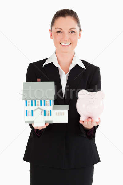 Pretty woman in suit holding a piggy bank and a miniature house while standing against a white backg Stock photo © wavebreak_media