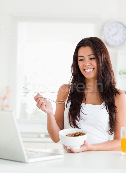 Good looking woman enjoying a bowl of cereal while relaxing with her laptop in the kitchen Stock photo © wavebreak_media