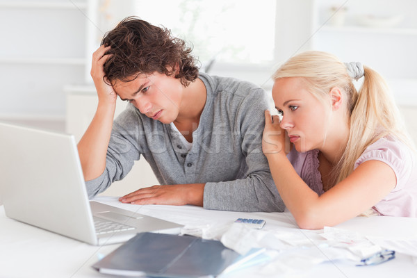Upset couple with bills and a notebook in their living room Stock photo © wavebreak_media