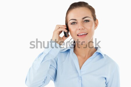 Stock photo: Businesswoman talking on her cellphone against a white background