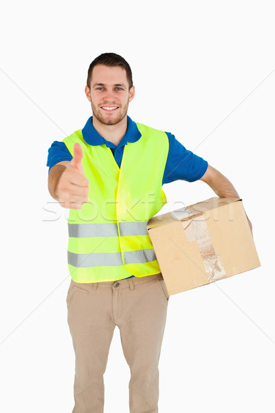 Smiling young delivery man giving thumb up against a white background Stock photo © wavebreak_media