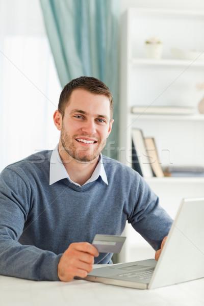 Foto stock: Sonriendo · jóvenes · masculina · tarjeta · de · crédito · cuaderno · ordenador