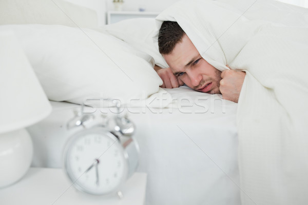 Man covering his ears while his alarm clock is ringing in his bedroom Stock photo © wavebreak_media