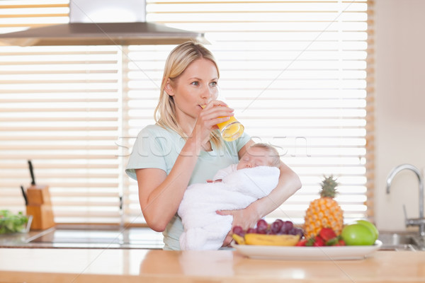 Woman taking a sip of orange juice while holding her baby Stock photo © wavebreak_media