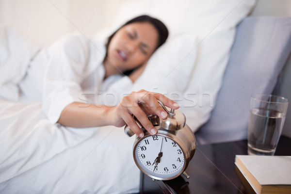 Alarm clock almost falling off the bedside locker while being turned off by woman Stock photo © wavebreak_media