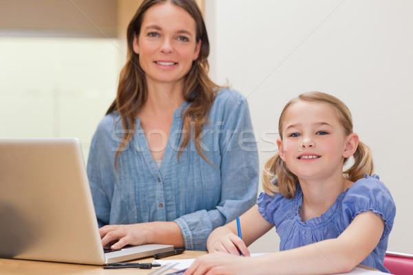 Dziewczyna praca domowa matka notebooka kuchnia komputera Zdjęcia stock © wavebreak_media