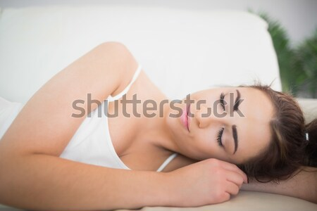 A woman lying on the bed, her head is on the pillow with her eyes open and smiling. Her hands are on Stock photo © wavebreak_media