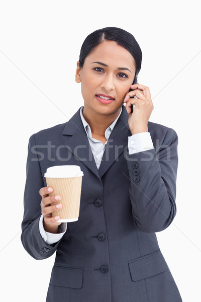 Close up of serious saleswoman with paper cup and cellphone against a white background Stock photo © wavebreak_media