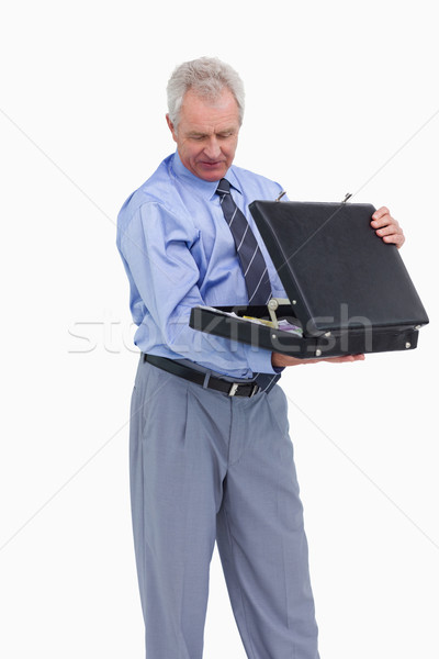 Stock photo: Mature tradesman looking into his suitcase against a white background