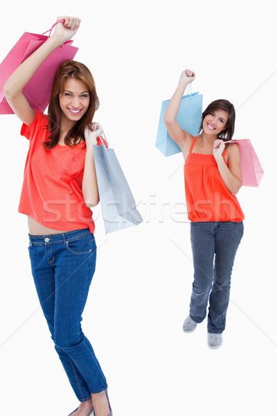 Teenage girl following a friend with purchase bags against a white background Stock photo © wavebreak_media