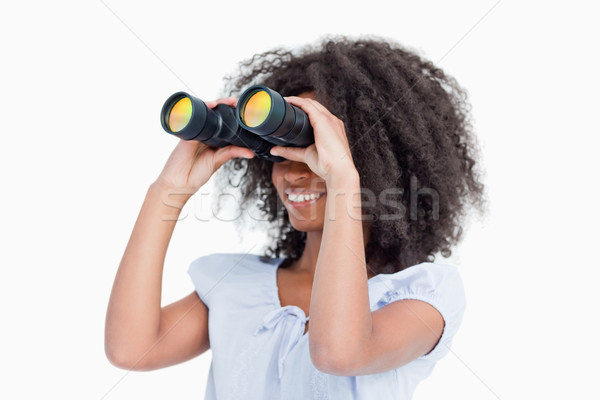 Young woman looking on the side through binoculars against a white background Stock photo © wavebreak_media