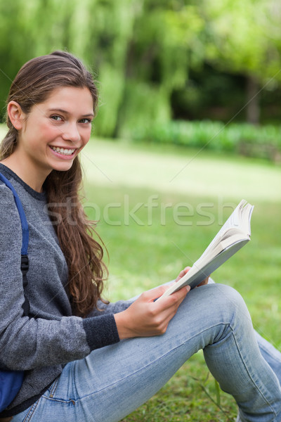 Young happy adult looking straight at the camera while beaming and reading a book Stock photo © wavebreak_media