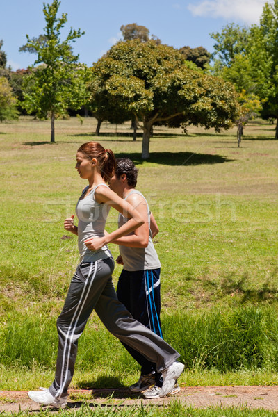 Woman and a man jogging along side each other along a running trail with a view of trees and the sky Stock photo © wavebreak_media