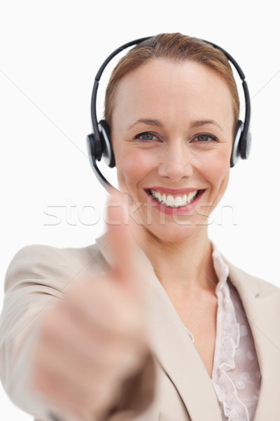 Portrait of a businesswoman with a headset approving against white background Stock photo © wavebreak_media