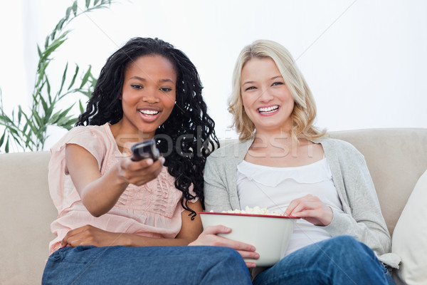 Dwie kobiety posiedzenia w dół popcorn telewizji pilota Zdjęcia stock © wavebreak_media